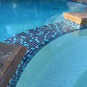 Spa waterline & spillway retiled w/glass 1x1 tiles.